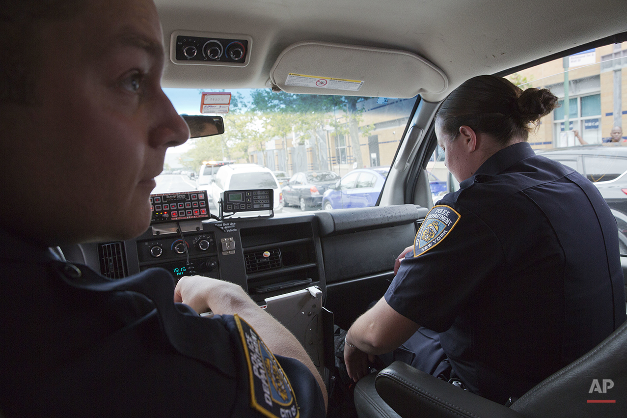 "Police officers Mary Gillespie, right, and Jessi D'Ambrosio of the 120th precinct sit in their patrol van at the Richmond Terrace houses in the Staten Island borough of New York, Thursday, July 7, 2016. In 2015, the city began assigning pairs of officers to specific neighborhoods, rather than having them rush from call to call across precincts. They are mandated to spend a third of their shift ""off-radio,"" talking with residents to forge relationships. The new approach was rolled out to the North Shore in December. (AP Photo/Mary Altaffer)"