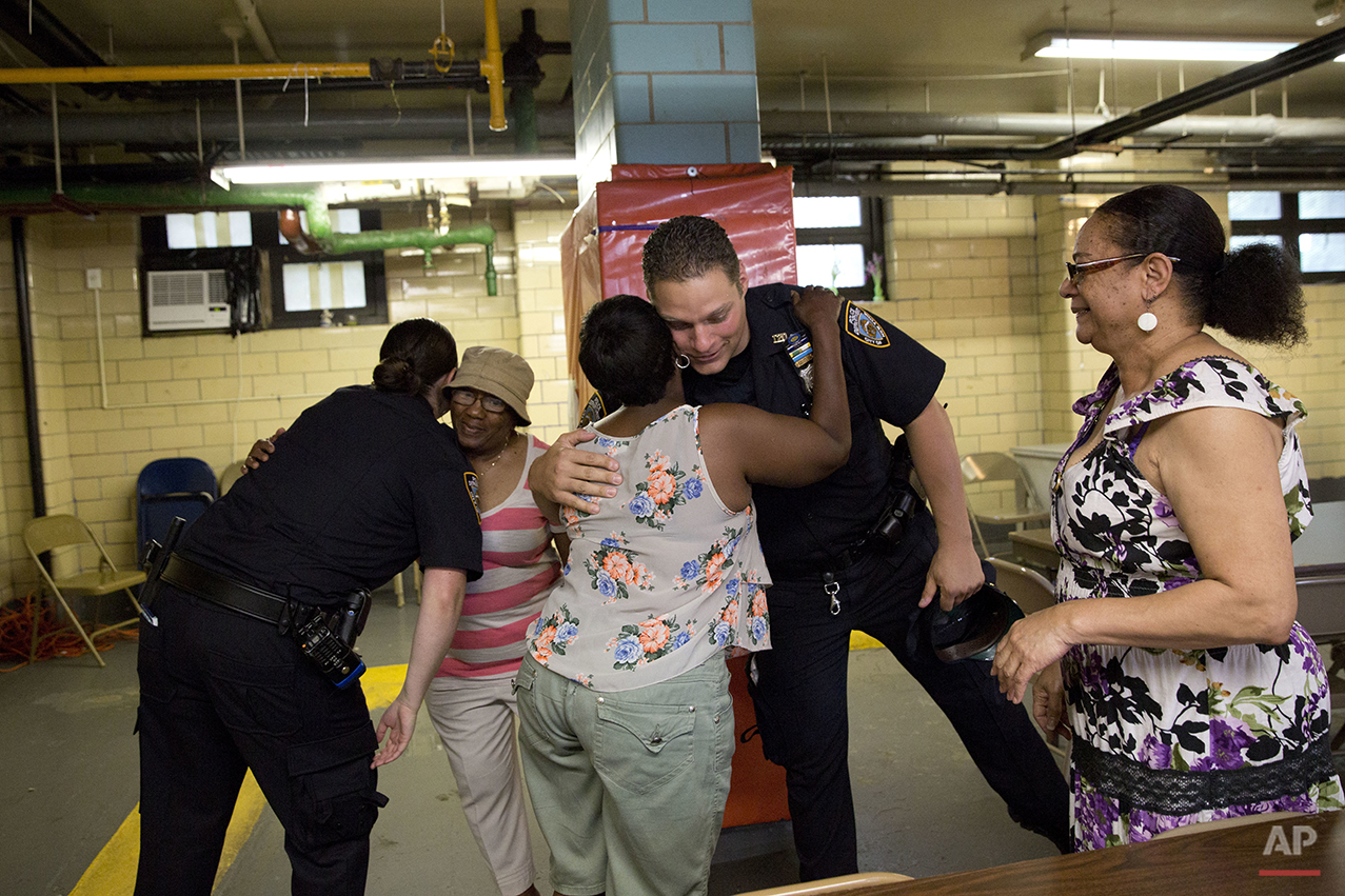 "Police officer Mary Gillespie, left, of the 120th precinct on the Staten Island borough of New York, hugs Richmond Terrace Houses resident Gloria Phillips as fellow officer Jessi D'Ambrosio, center, hugs Barbara Shiel on Thursday, July 7, 2016. At right is Eunice Love president of the Richmond Terrace Houses. Love recalls years of seeing officers without knowing who they were. But D'Ambrosio and Gillespie? ""They're such homeboy, homegirl,"" she says. ""They know how to get along with people and relate and we love that."" (AP Photo/Mary Altaffer)"