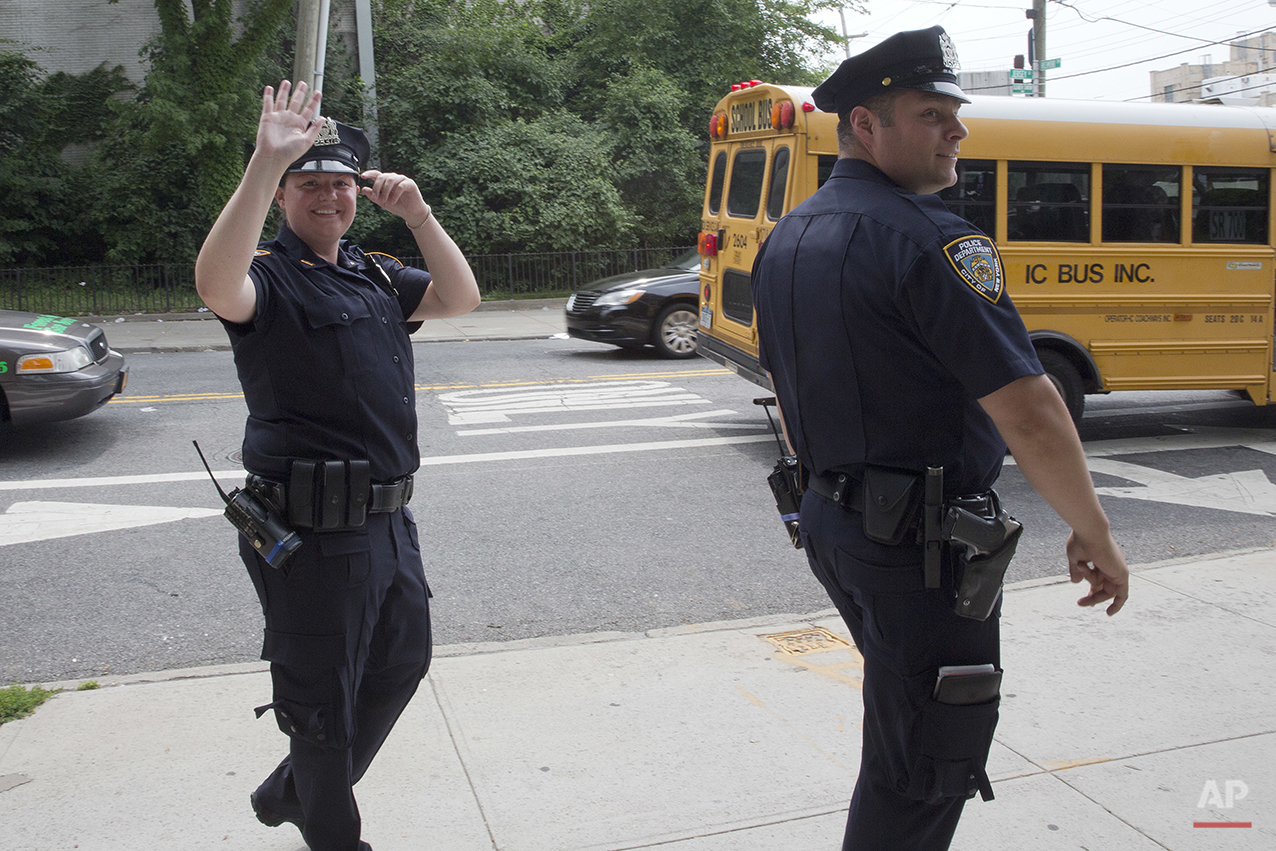 "Police officer Mary Gillespie, left, of the 120th precinct on Staten Island borough of New York, waves at a residents of the Richmond Terrace Houses while on patrol with fellow officer Jessi D'Ambrosio on Thursday, July 7, 2016. In 2015, the city began assigning pairs of officers to specific neighborhoods, rather than having them rush from call to call across precincts. They are mandated to spend a third of their shift ""off-radio,"" talking with residents to forge relationships. The new approach was rolled out to the North Shore in December. (AP Photo/Mary Altaffer)"