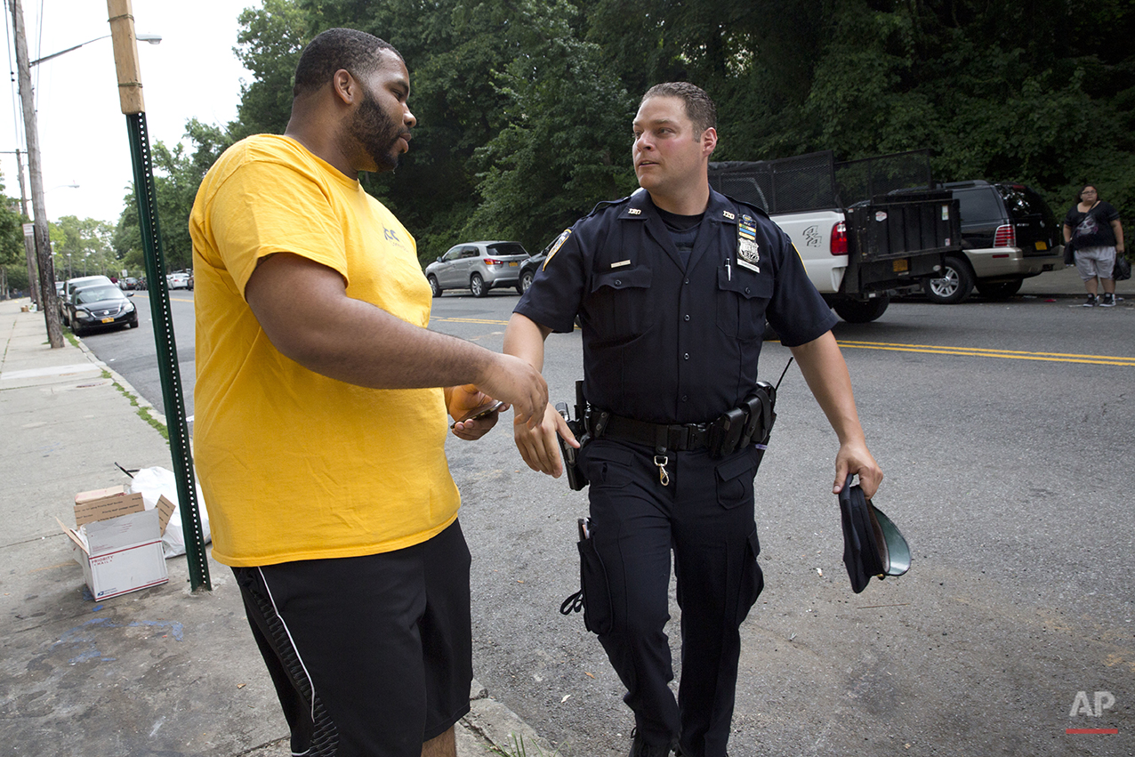 "Police officer Jessi D'Ambrosio, left, of the 120th precinct in the Staten Island borough of New York, speaks to a resident while on patrol at the Richmond Terrace Houses, Thursday, July 7, 2016. D'Ambrosio, 32, and his partner, Mary Gillespie, 28, are the new ""neighborhood coordinating officers"" for the six-building project where Eric Garner once lived. Jersey Street, with a reputation for crime, runs the length of a complex, most of whose residents are black. ""We want them to feel comfortable with us and that's what we're building on,"" Gillespie says. (AP Photo/Mary Altaffer)"
