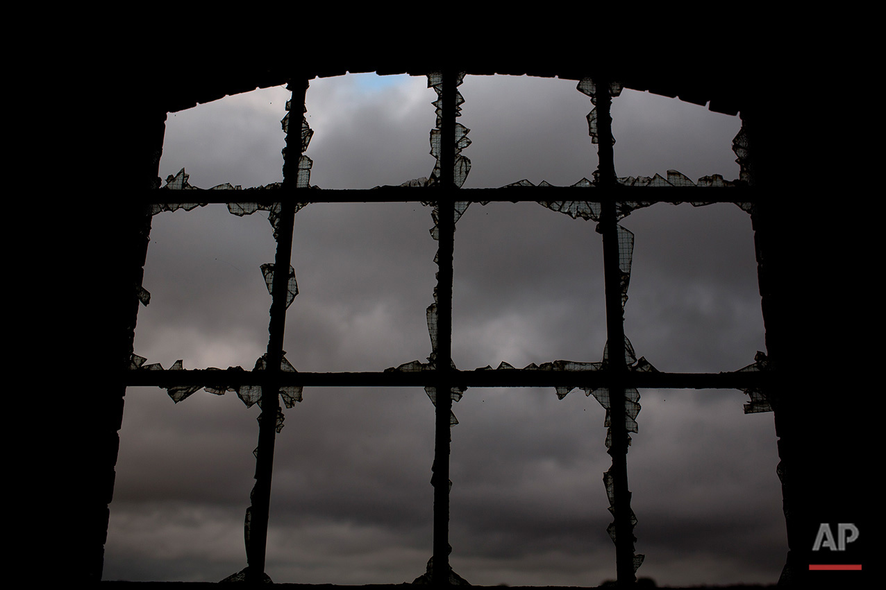 In this Thursday, June 30, 2016 photo, a cloudy sky is seen through the broken glasses of a window, inside the workshop building of the Penallta colliery in Hengoed, South Wales.  (AP Photo/Emilio Morenatti)