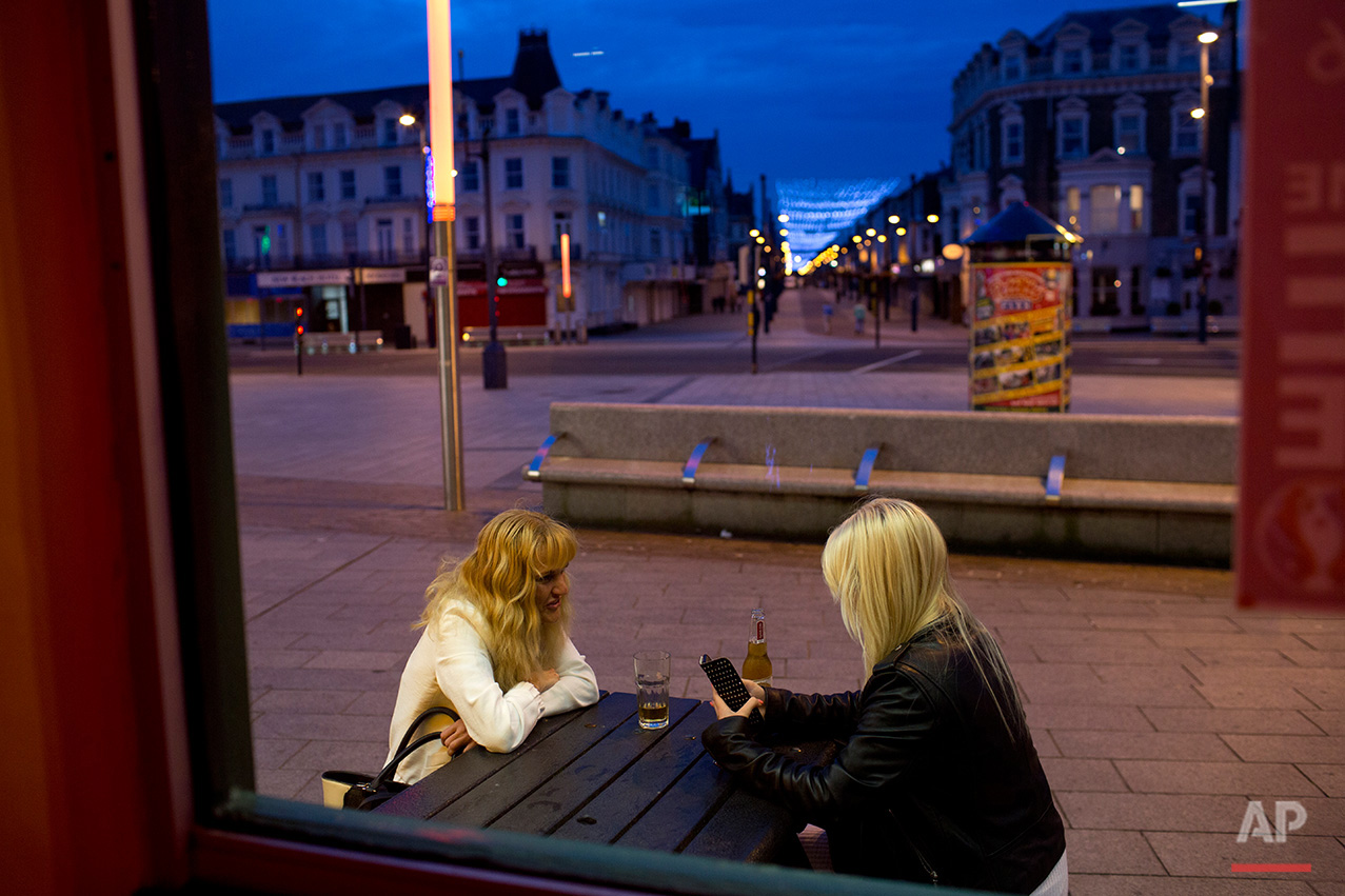 In this Wednesday, July 6, 2016 photo, two woman sit outside a pub at Great Yarmouth, East of England. On a rare blue-sky day in Great Yarmouth, a quintessentially English seaside resort with squeaky-floored hotels and screeching seagulls, the mostly elderly people strolling along the beach longed for a bygone era. (AP Photo/Emilio Morenatti)