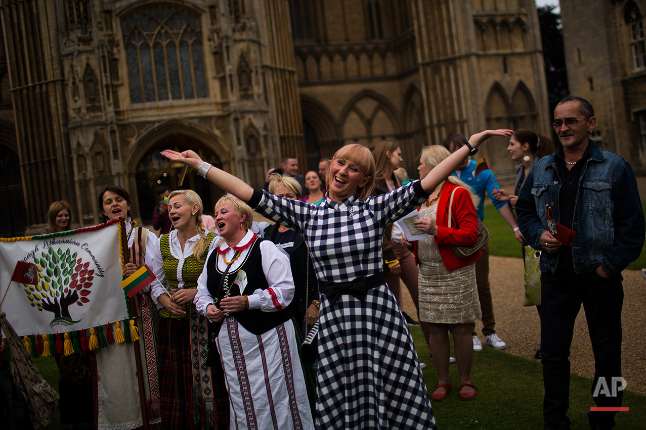 In this Wednesday, July 6, 2016 photo,  Lithuanians sign their national anthem during a ceremony in front of the Saint Peter's Cathedral in downtown Peterborough, East of England. On Wednesday about 100 Lithuanians, some wearing traditional costumes, celebrated the Baltic country's national holiday in the center of the city. Standing in front Peterborough's majestic gothic cathedral, a symbol of the city, they waved Lithuanian flags and sang their national anthem. (AP Photo/Emilio Morenatti)