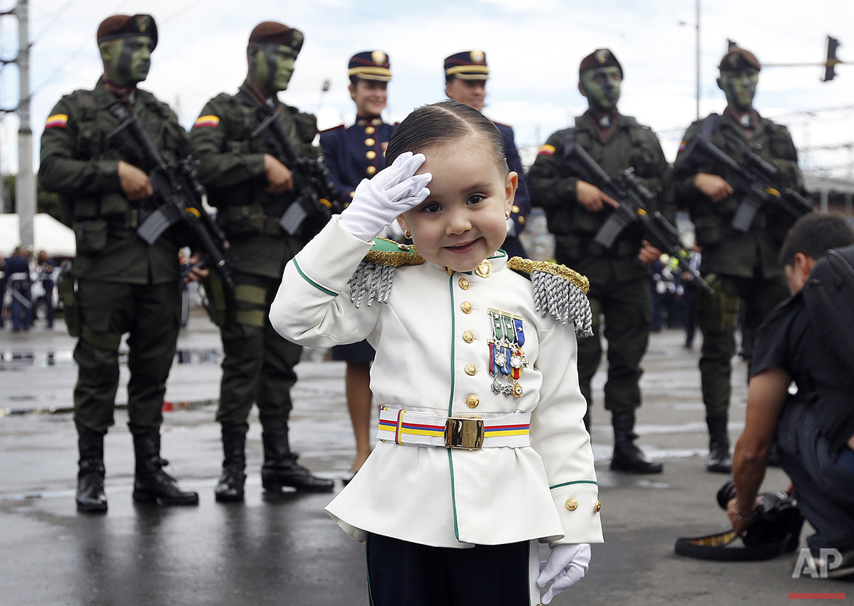 Gabriela Gomez, 3, poses for a photo wearing a military costume before the start of a military parade celebrating the 206th anniversary of the country's independence from Spain, in Bogota, Colombia, Wednesday, July 20, 2016. (AP Photo/Fernando Vergara)