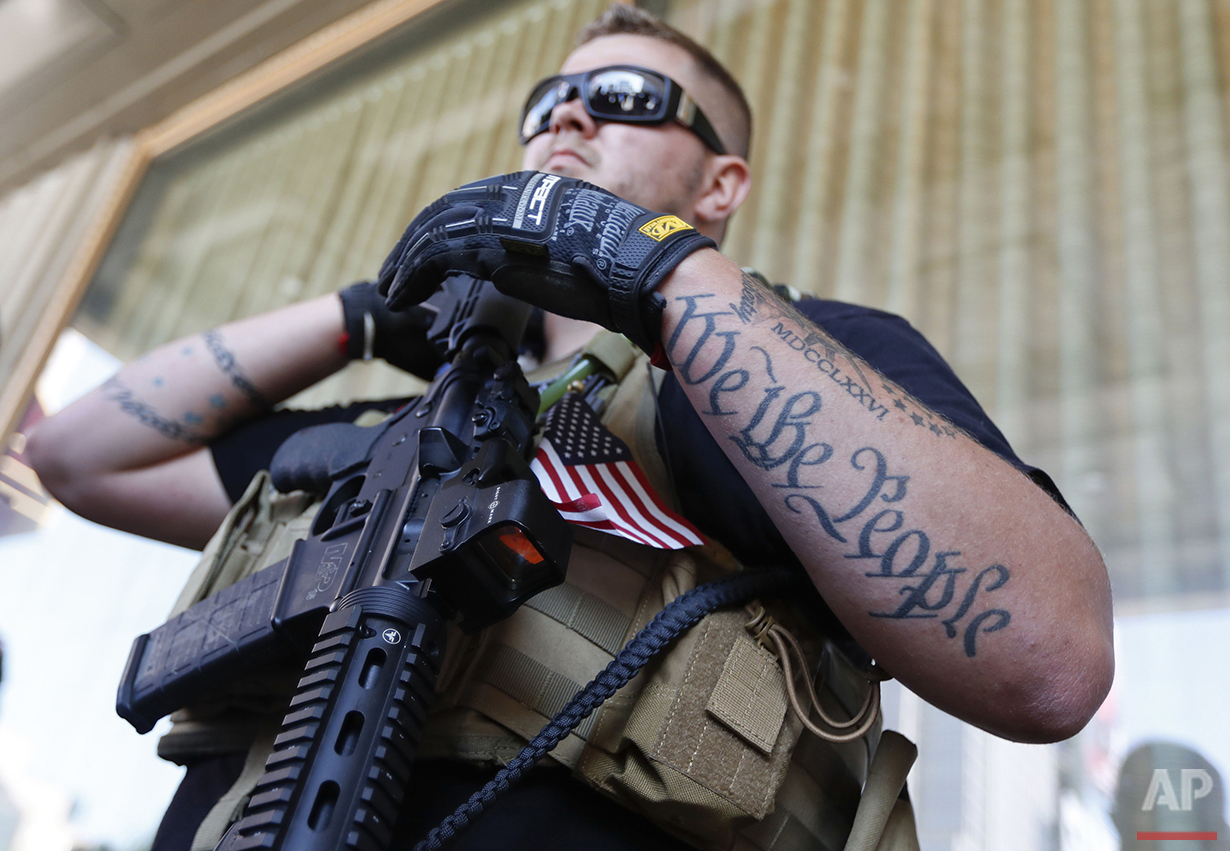 Tevor Leis, exercising his Ohio open carry rights, stands armed in Public Square on Tuesday, July 19, 2016, in Cleveland, during the second day of the Republican convention. (AP Photo/John Minchillo)
