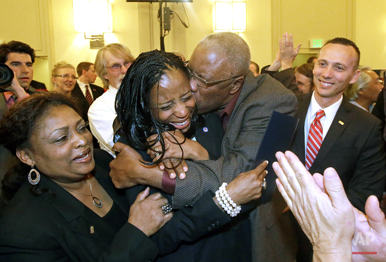 In this Nov. 4, 2014, photo, Republican Mia Love celebrates with her father, Jean Maxime Bourdeau, after winning the race for Utah's 4th Congressional District during election night, in Salt Lake City. Utah has never had a female U.S. senator and only four women have served in the U.S. House of Representatives, including Rep. Love, who now serves along with three men holding the remaining congressional jobs. (AP Photo/Rick Bowmer)