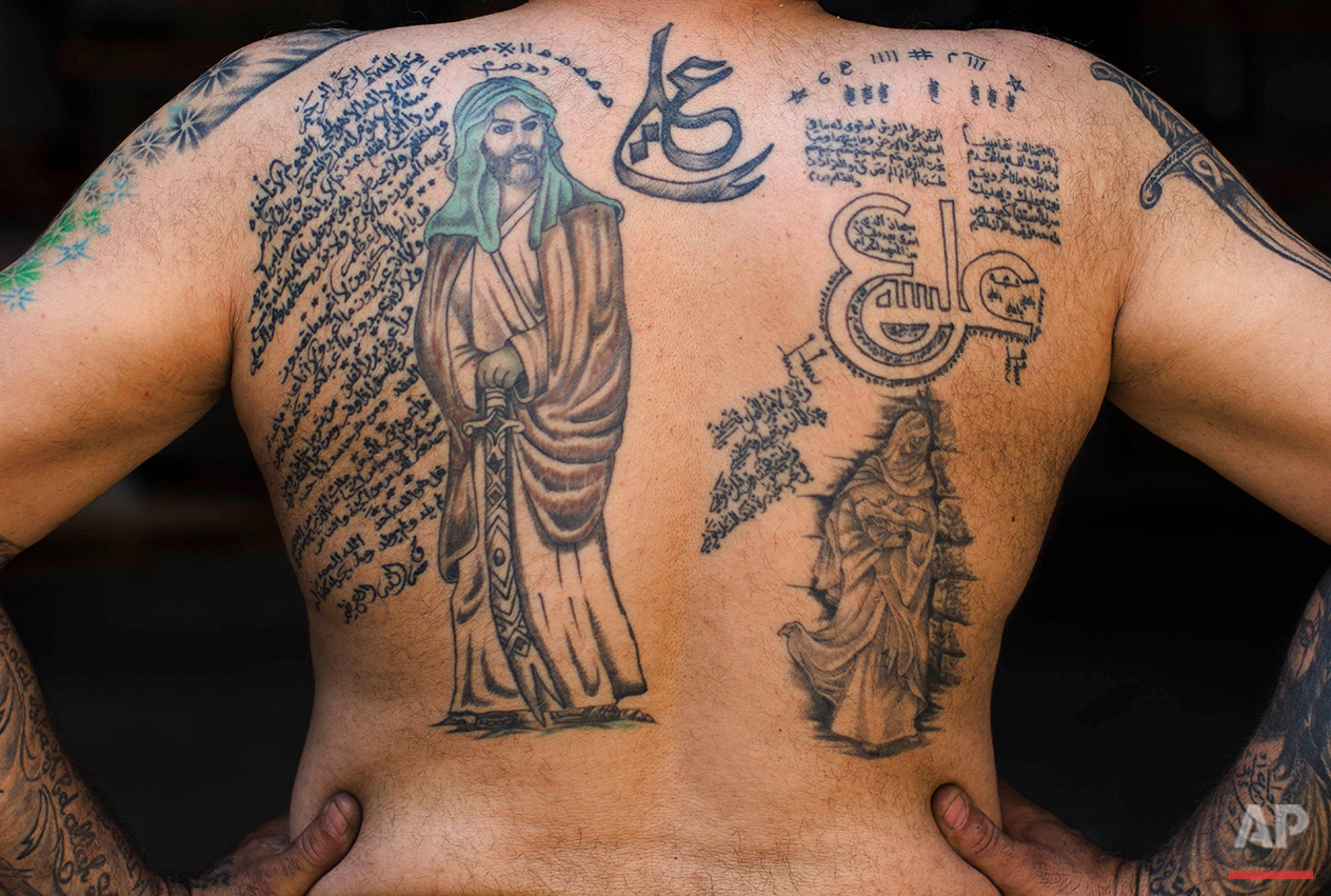 In this Tuesday, May 10, 2016 photo, Ali Hussein Nasreddine, 50, poses for a photo showing off his tattoos of Shiite Muslim religious slogans and Shiite Muslims' first Imam Ali, in the southern suburb of Beirut. (AP Photo/Hassan Ammar)