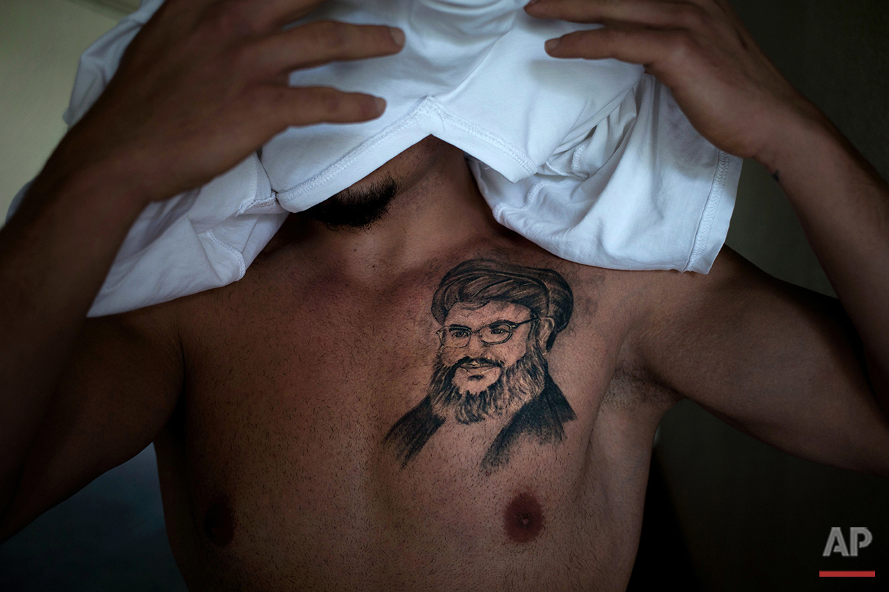 """In this Tuesday, May 24, 2016 photo, Tayseer, 30, civil servant, covers his face as he poses for a photo showing a tattoo of Hezbollah leader Hassan Nasrallah, in the southern suburb of Beirut. He got it five months ago as an expression of """"deep love"""" for the man he says is protecting Lebanon from Islamic State group and other extremists fighting in neighboring countries. (AP Photo/Hassan Ammar)"""