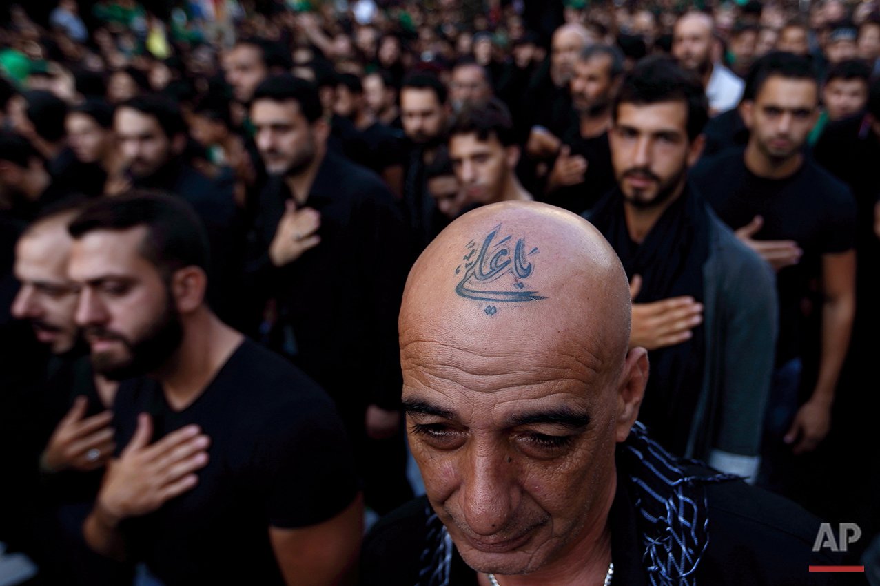 """In this Saturday, Oct. 24, 2015 photo, a Lebanese Shiite supporter of Hezbollah with a tattoo on his head that reads in Arabic, """"Oh Ali"""", beats his chest during the holy day of Ashoura, in the southern suburb of Beirut. A growing number of Shiite Muslims in Lebanon are getting tattoos with religious and other Shiite symbols since the civil war in neighboring Syria broke out five years ago, fanning sectarian flames across the region. (AP Photo/Hassan Ammar)"""
