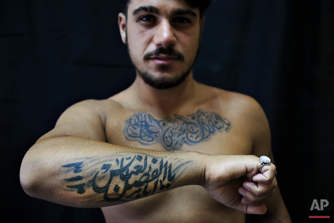 """In this Monday, July 18, 2016 photo, Alodi Issa, 22, poses for a photo showing off his tattoos with Shiite Muslim religious slogans in the southern suburb of Beirut. The tattoo in Arabic reads, """"Oh, the revenge for Hussein. Ali, Fatima. 313, Oh Abu Fadel al-Abbas."""" (AP Photo/Hassan Ammar)"""