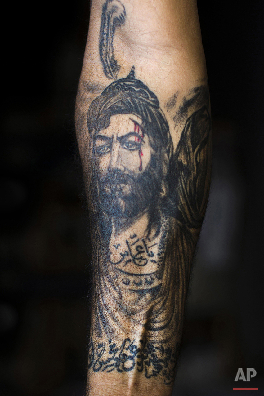 """In this Tuesday, May 10, 2016 photo, Ali Hussein Nasreddine, 50, poses for a photo showing off his tattoo of Imam Abbas with blood on his face in the southern suburb of Beirut. The tattoo in Arabic reads, """"Oh Abbas."""" (AP Photo/Hassan Ammar)"""
