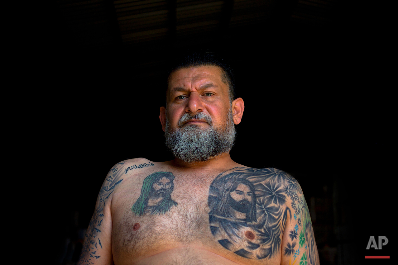 In this Tuesday, May 31, 2016 photo, Ali Hussein Nasreddine, 50, poses for a photo showing his tattoo of Shiite Muslims' first Imam Ali, and his son Imam Hussein, the grandson of the Prophet Muhammed, in the southern suburb of Beirut. (AP Photo/Hassan Ammar)