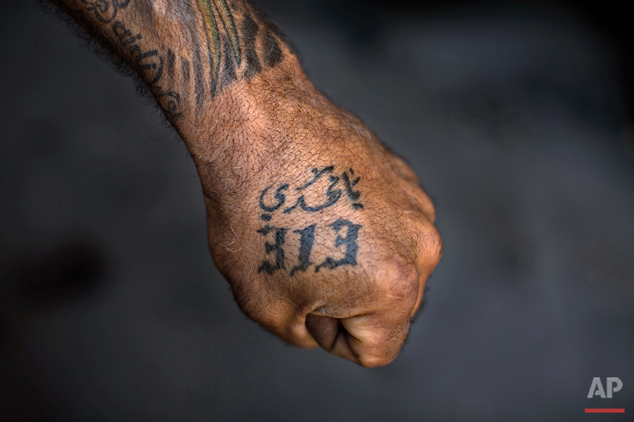 """In this Tuesday, May 10, 2016 photo, Ali Hussein Nasreddine, 50, poses for a photo showing off his tattoos with Shiite Muslim religious slogans in the southern suburb of Beirut. The tattoo in Arabic reads, """"Oh Mahdi, 313."""" (AP Photo/Hassan Ammar)"""