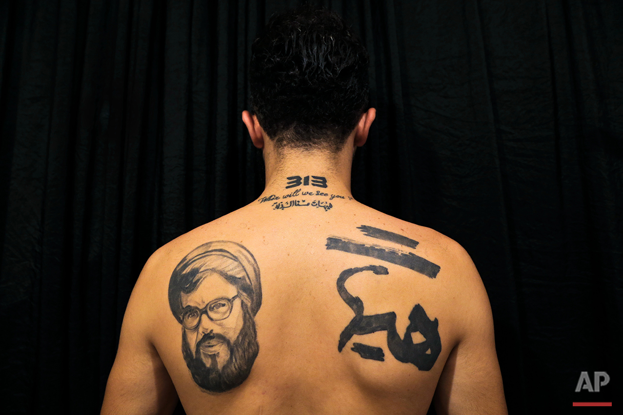 """In this Tuesday, July 19, 2016 photo, Hamza, 25, poses for a photo showing off his tattoos of Hezbollah leader Hassan Nasrallah and Shiite Muslim religious slogans in the southern suburb of Beirut. The tattoo in Arabic reads, """"It is impossible to humiliate us."""" (AP Photo/Hassan Ammar)"""