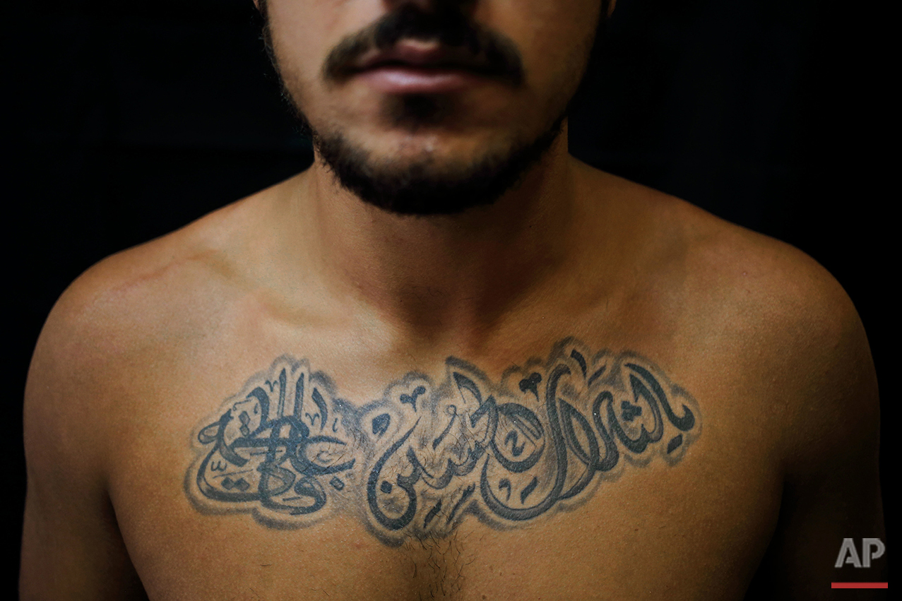 """In this Monday, July 18, 2016 photo, Alodi Issa, 22, poses for a photo showing off his tattoos with Shiite Muslim religious slogansin the southern suburb of Beirut. The tattoo in Arabic reads, """"Oh, the revenge for Hussein. Ali, Fatima."""" (AP Photo/Hassan Ammar)"""