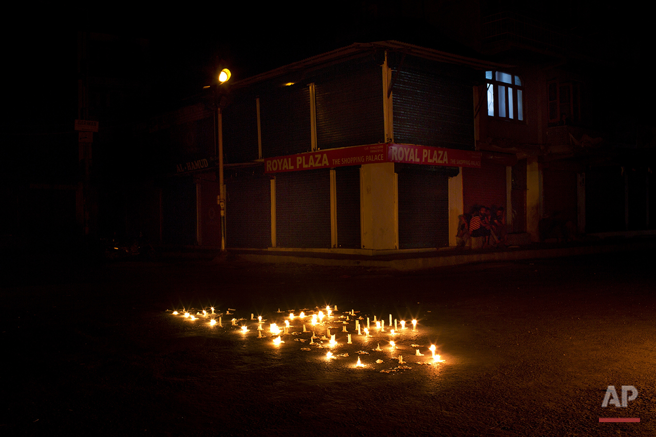 In this July 24, 2016 photo, candles used during a peaceful protest organized by Kashmiri separatist burn in the middle of a street in downtown Srinagar, India-controlled Kashmir. (AP Photo/Bernat Armangue)