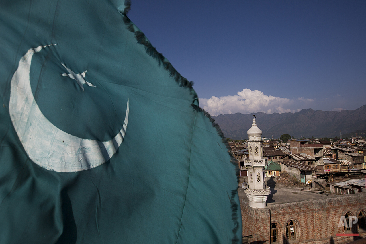In this July 24, 2016 photo, a green Islamic flag flutters from a rooftop in Srinagar, India-controlled Kashmir. Islam has been rooted in the region since the 14th century. (AP Photo/Bernat Armangue)