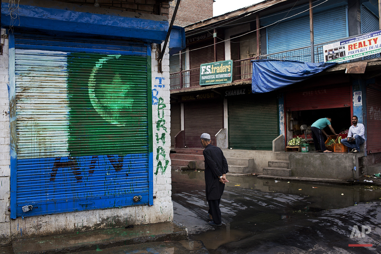 In this July 25, 2016 photo, a Pakistani flag is painted on a security shutter of a shop in downtown Srinagar, India-controlled Kashmir. Kashmir, a predominantly Muslim region, is divided between India and Pakistan, but both claim it in its entirety. The rivals have fought two wars over control of Kashmir since independence from Britain in 1947. (AP Photo/Bernat Armangue)