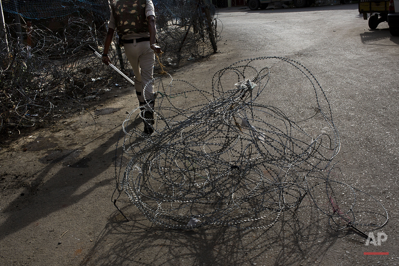 In this July 23, 2016 photo, an Indian paramilitary soldier drags barbed wire at the end of a daylong curfew in Srinagar, India-controlled Kashmir. (AP Photo/Bernat Armangue)