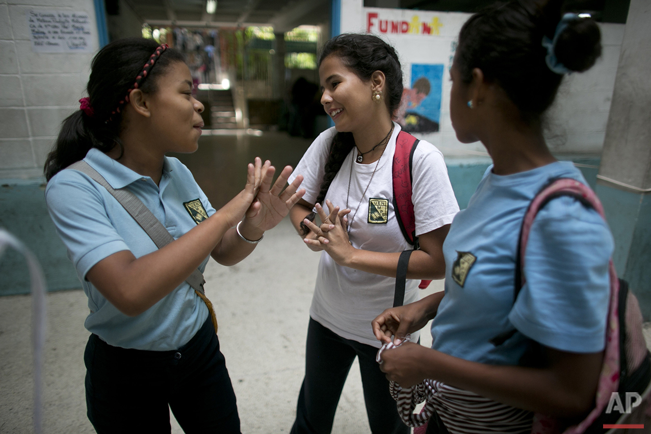 """In this May 31, 2016 photo, Maria Arias, center, shares a moment with classmates as they wait for their teacher to arrive for class at their public high school in Caracas, Venezuela. Arias lives in a violent neighborhood and has grown accustomed to her teachers not showing up for class. """"It's a trap, the 14 year-old complained. You risk your life to be here and end up waiting around for hours doing nothing. But you have to keep coming because it's the only way out."""" (AP Photo/Ariana Cubillos)"""