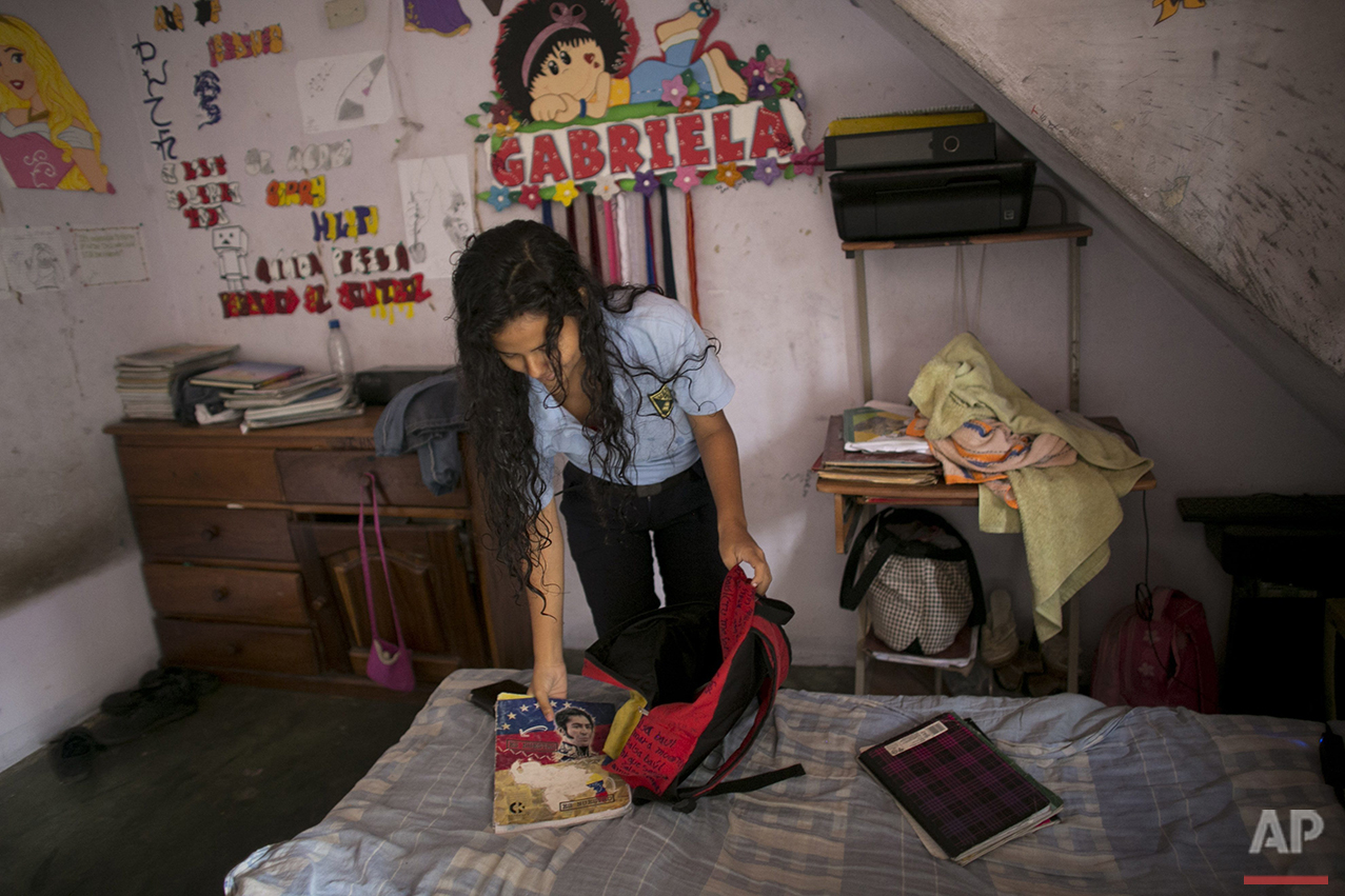 """In this June 1, 2016, Maria Arias packs her backpack in her bedroom, decorated with her middle name """"Gabriela,"""" in Caracas, Venezuela. Chatty and so studious her classmates call her """"Wikipedia."""" Arias started the year at a school with dreams of becoming an accountant and moving to Paris. Her parents saved up to buy her new notebooks, one for each subject, but nine months later, they remain mostly empty due to her teachers not showing up for class, or entire school days being cancelled. (AP Photo/Ariana Cubillos)"""