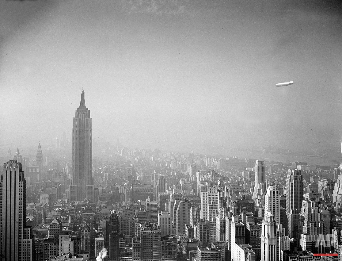 The German-built zeppelin Hindenburg, right, floats over the Manhattan skyline on Aug. 8, 1936. The Empire State Building, measuring 1,250 feet in height, can be seen at left.  (AP Photo)