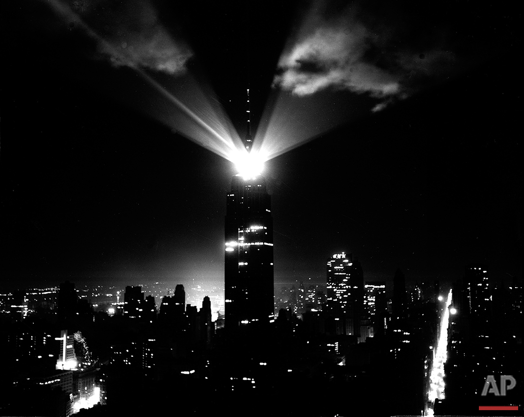A new beacon light atop the Empire State Building in New York City, visible for 80 miles, lights up clouds as they revolve during a test on April 11, 1956.  The glow at left of the building is from Times Square.  Madison Ave., is at right.  (AP Photo)