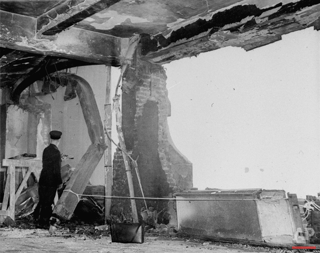 A fireman stands beside a twisted girder as he examines the gaping holes in the north side of the Empire State Building on the 79th floor, evidence of the terrific impact with which a B-25 Army bomber crashed into the structure in New York, July 28, 1945.  (AP Photo)