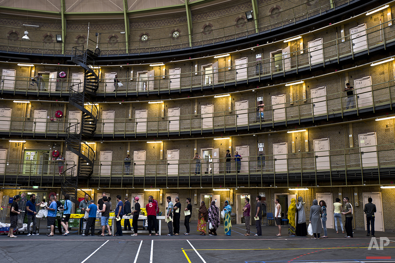 In this Wednesday, April 20, 2016 photo, refugees and migrants line up to receive their lunch at the former prison of De Koepel in Haarlem, Netherlands. (AP Photo/Muhammed Muheisen)
