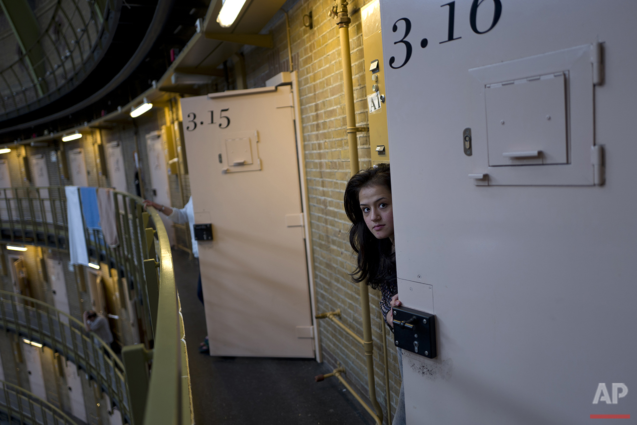 In this Saturday, May 7, 2016 photo, Afghan refugee Shazia Lutfi, 19, peeks through the door of her room at the former prison of De Koepel in Haarlem, Netherlands. The government has let Belgium and Norway put prisoners in its empty cells and now, amid the huge flow of migrants into Europe, several Dutch prisons have been temporarily pressed into service as asylum seeker centers. (AP Photo/Muhammed Muheisen)