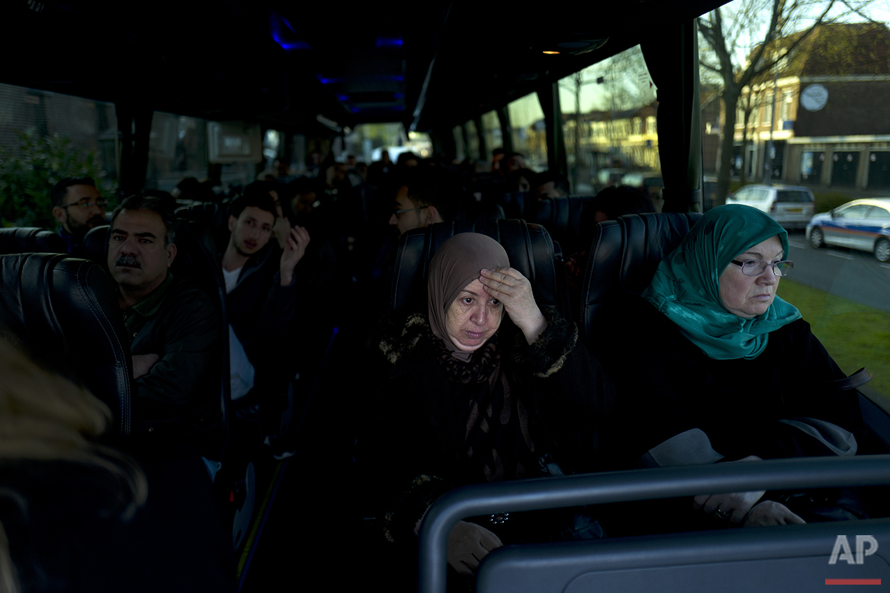 In this Friday, May 6, 2016 photo, Iraqi refugee Fatima Hussein, 65, reacts while she and others wait in a bus heading to have a government interview for their asylum seeking process outside the former prison of De Koepel in Haarlem, Netherlands. (AP Photo/Muhammed Muheisen)