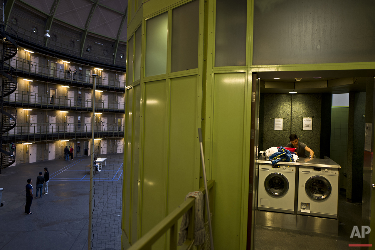 In this Monday, April 25, 2016 photo, In this Sunday, May 1, 2016 photo, Afghan refugee Siratullah Hayatullah, 23, washes in a washing room in the former prison of De Koepel in Haarlem, Netherlands. (AP Photo/Muhammed Muheisen)