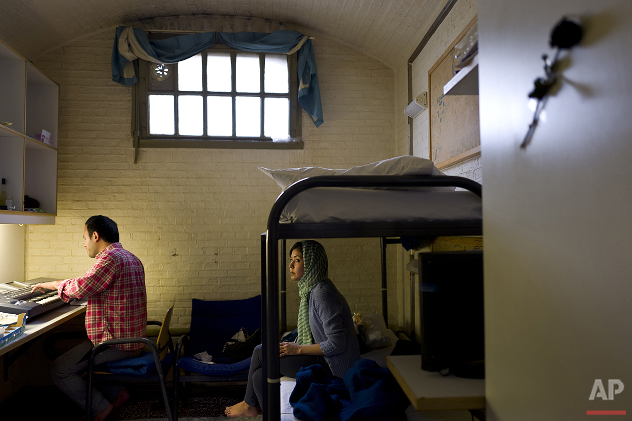 In this Wednesday, April 6, 2016 photo, Afghan refugee Hamed Karmi, 27, plays keyboard next to his wife Farishta Morahami, 25, sitting on a bed inside their room at the former prison of De Koepel in Haarlem, Netherlands. (AP Photo/Muhammed Muheisen)