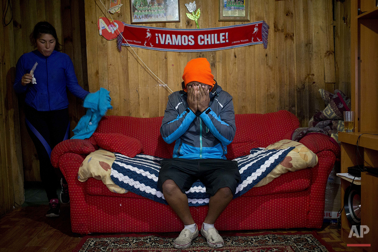 "In this May 10, 2016 photo, diver Jose Luis Cifuentes covers his face in exhaustion and frustration saying he has no money to buy food, inside his mother-in-law's home in Ancud, Chiloe Island, Chile, during the country's worst ever ""red tide"" environmental disaster. Chile is among the world's top suppliers of salmon and fishing is the backbone of the economy for many communities along the country's long coast. (AP Photo/Esteban Felix)"
