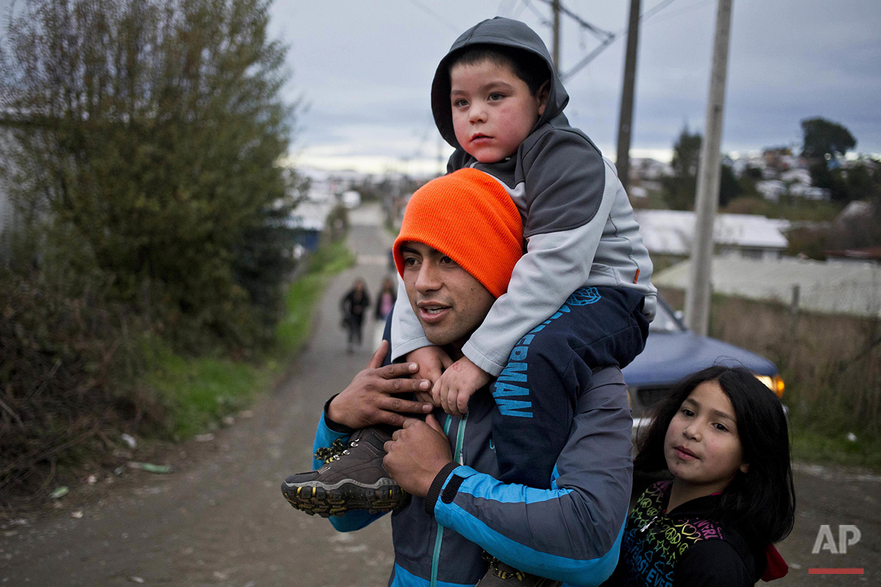 "In this May 12, 2016 photo, diver Jose Luis Cifuentes, shoulders his five-year-old stepson Martin, as he walks with his young sister-in-law Escarleth Araneda, to a protest in Ancud, in Chiloe Island, Chile, during the country's worst ever ""red tide"" environmental disaster. Food and gasoline have been scarce after small-scale fishermen blocked the island from the mainland, lighting flaming barricades for days to demand more compensation from the government. (AP Photo/Esteban Felix)"