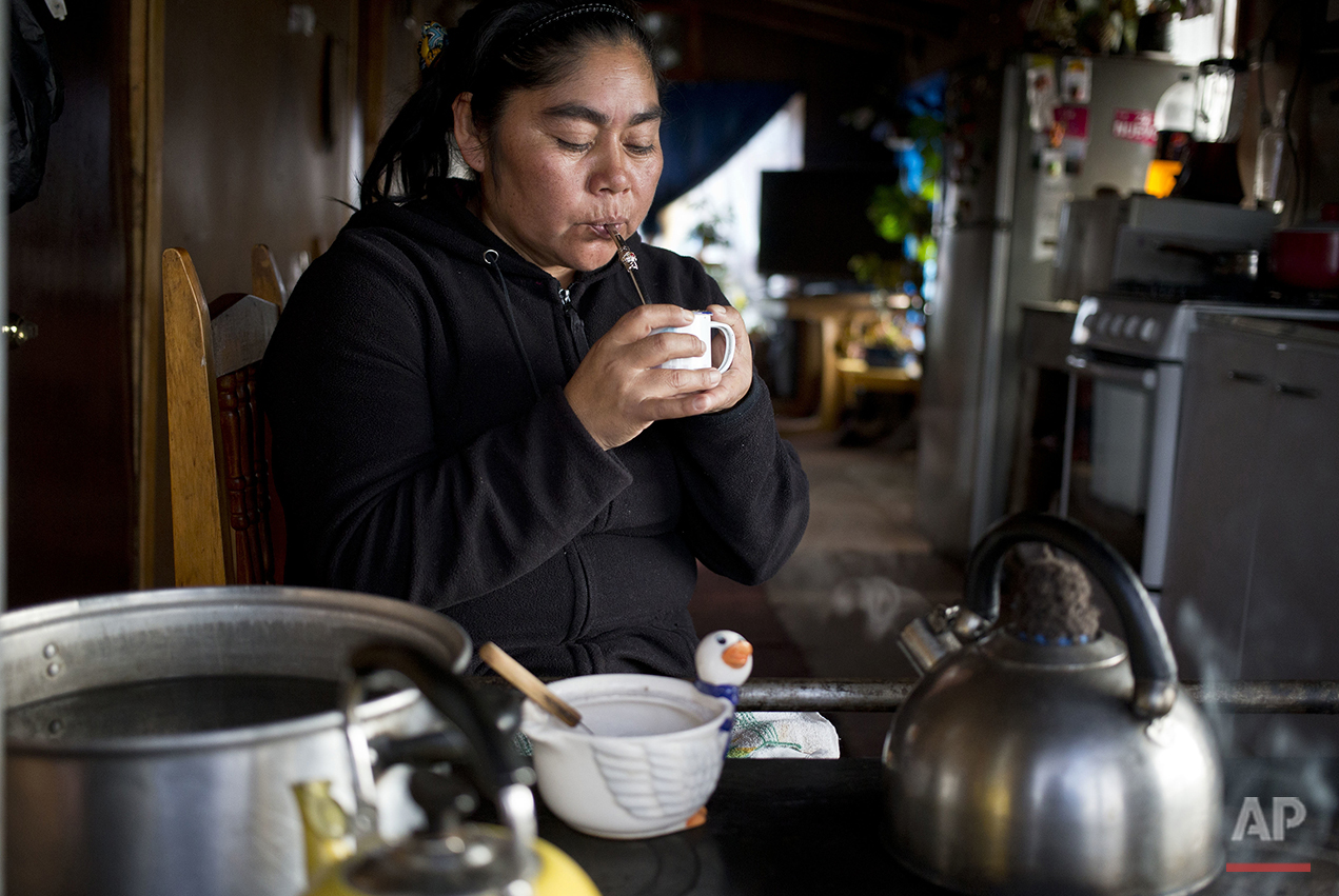 "In this May 10, 2016 photo, small scale fisherwoman Marisol Millaquien sips on a cup of mate, an herbal tea, in her home in the fishing village Quetalmahue, on Chile's Chiloe Island. Like many other residents, she's in disbelief of scientists who say that the red tide environmental disaster that's killing fish was caused by warmer temperatures stemming from this year's ""Godzilla"" El Nino weather phenomenon. Instead, she believes that commercial salmon farms in Chile are to blame for dumping contaminated fish near the coast. (AP Photo/Esteban Felix)"