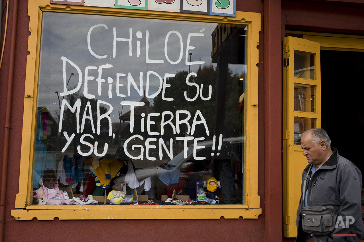"This May 10, 2015 photo shows a storefront window emblazoned with a message that reads in Spanish ""Chiloe defends its sea, its land, and its people"" in Ancud, in Chile's Chiloe island, during the country's worst ever ""red tide"" environmental disaster. The government has offered about $220 a month to some 5,000 local fishermen as compensation, but they're demanding twice that, saying the offer isn't enough to cover basic needs. (AP Photo/Esteban Felix)"