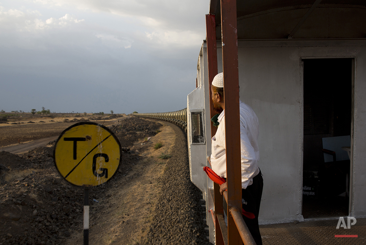 "In this May 9, 2016, photo, Sikandar Nabi Sahab, guard of the Jaldoot water train, peers out from his cabin as the train rolls out of the Miraj railway station, Miraj, 340 kilometes (211 miles) from Latur, in the Indian state of Maharashtra. Many trains pull into Latur's railroad station but none is as eagerly awaited as this train that pulls into the parched town in the dead of the night. That train called ""Jaldoot"" or the Messenger of Water brings millions of liters of the precious liquid that the drought-plagued central Indian district so desperately needs. (AP Photo/Manish Swarup)"