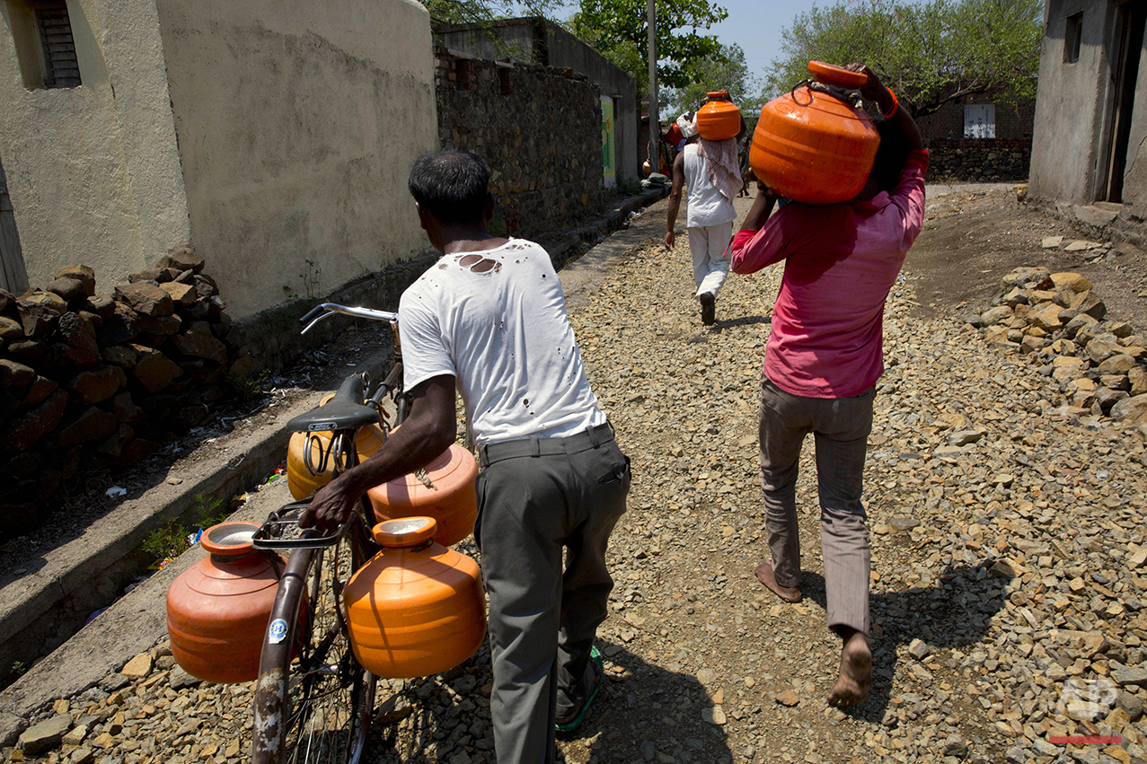 "In this May 10, 2016, photo, villagers carry plastic containers holding potable water which is provided by the Jaldoot water train in Latur, in the Indian state of Maharashtra. Many trains pull into Latur's railroad station but none is as eagerly awaited as this train that pulls into the parched town in the dead of the night. That train called ""Jaldoot"" or the Messenger of Water brings millions of liters of the precious liquid that the drought-plagued central Indian district so desperately needs. (AP Photo/Manish Swarup)"