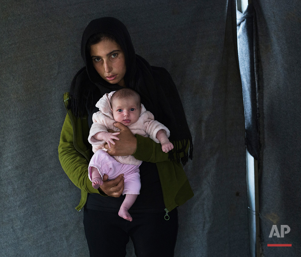 In this picture made on Thursday, May 12, 2016, 17-years-old Soumaya Zallaan, a Syrian mother from the city of Deir ez-Zor , poses with her baby girl Ritag in a tent made of blankets given by the UNCHR at the refugee camp of the northern Greek border point of Idomeni. Soumaya Zallaan is one of the dozens of refugee women that gave birth while stranded in Idomeni after the Greek- Macedonian border was closed in early March 2016. Ritag, the family's first child, was born on Wednesday, April 20, 2016 in the hospital of the nearby town of Policastro. The three member family wants to go to Germany.(AP Photo/Petros Giannakouris)