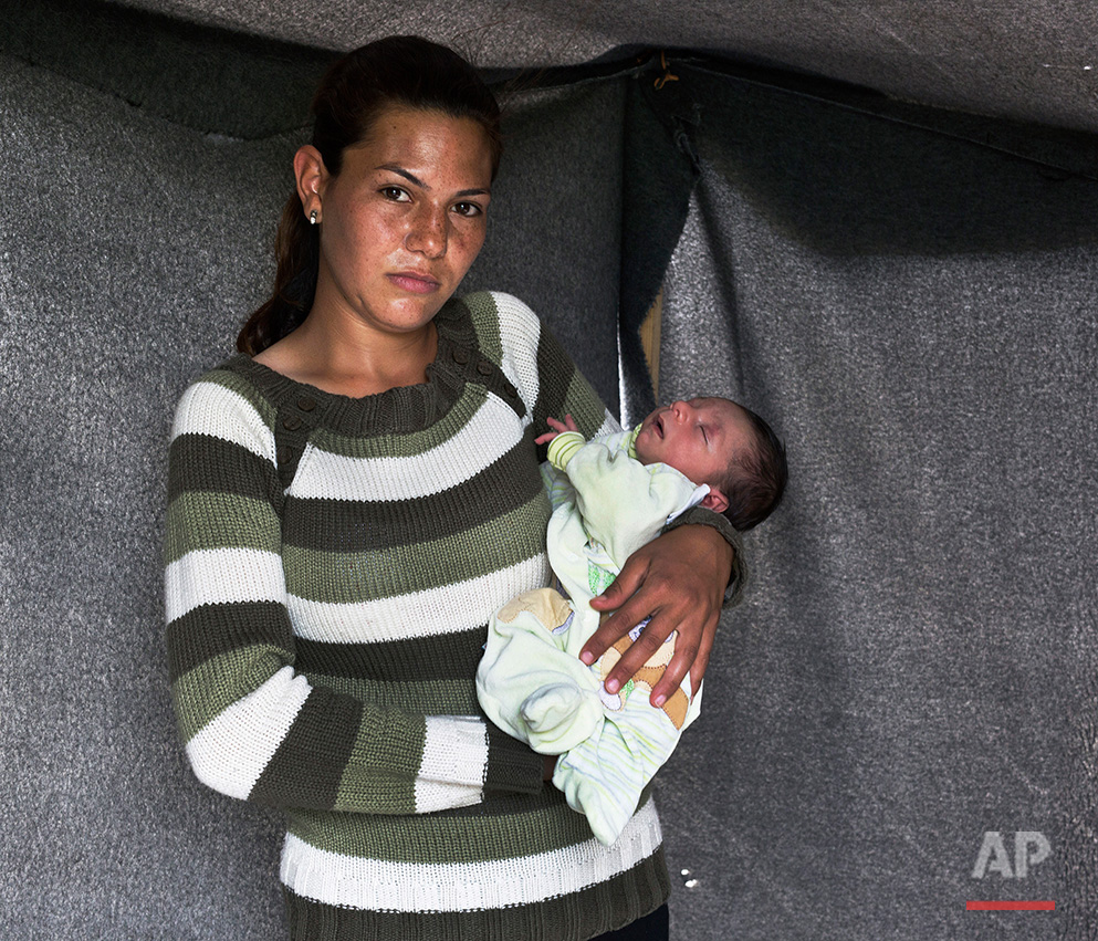 In this picture made on Sunday, May 15, 2016, 23-year-old Nariman, a Kurdish-Syrian mother from Kobani, poses with her baby boy Raman in a tent made of blankets given by the UNCHR at the refugee camp of the northern Greek border point of Idomeni. Noriman is one of the dozens of refugee women that gave birth while stranded in Idomeni after the Greek- Macedonian border was closed in early March 2016. Raman, the family's first child, was born on Thursday, March 31, 2016 in the hospital of the nearby town of Kilkis. The three member family wants to go to Germany or Spain. (AP Photo/Petros Giannakouris)