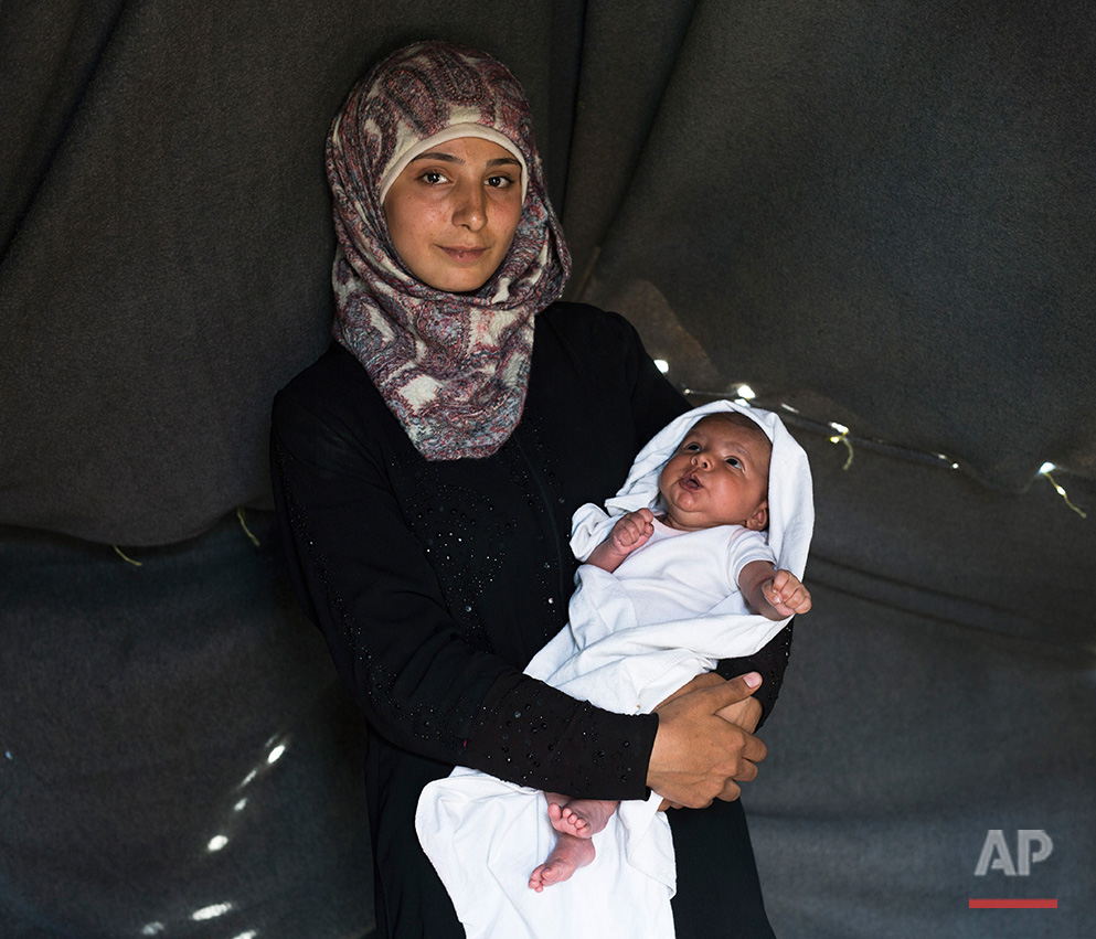 In this picture made on Saturday, May 14, 2016, 19-years-old Farah Sheikh Ahmed a Syrian mother from the city of Idlib poses with her baby girl Maram in a tent made of blankets given by the UNCHR at the refugee camp of the northern Greek border point of Idomeni. Farah Sheikh Ahmed is one of the dozens of refugee women that gave birth while stranded in Idomeni after the Greek- Macedonian border was closed in early March 2016. Maram the family's first child, was born on Wednesday, April 20, 2016 in the hospital of the nearby town of Kilkis. The three member family wants to go to Germany. (AP Photo/Petros Giannakouris)