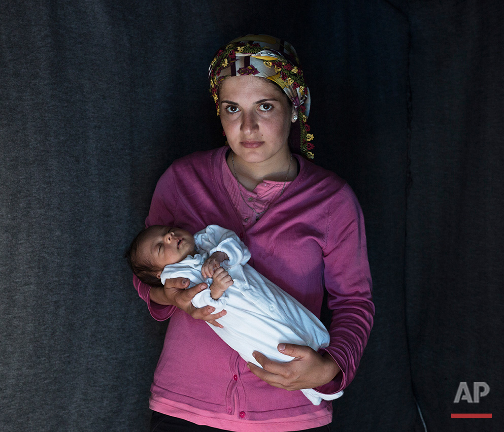 In this picture made on Friday, May 16, 2016, 23-year-old Rojin, a Kurdish-Syrian mother from the city of Qamishli, Syria  poses with her baby girl Beritan in a tent made of blankets given by the UNCHR at the refugee camp of the northern Greek border point of Idomeni. Rojin is one of the dozens of refugee women that gave birth while stranded in Idomeni after the Greek- Macedonian border was closed in early March 2016. Berating, the family's first child, was born on Sunday, April 10, 2016 in the hospital of the nearby town of Kilkis. The three member family wants to go to Switzerland. (AP Photo/Petros Giannakouris)