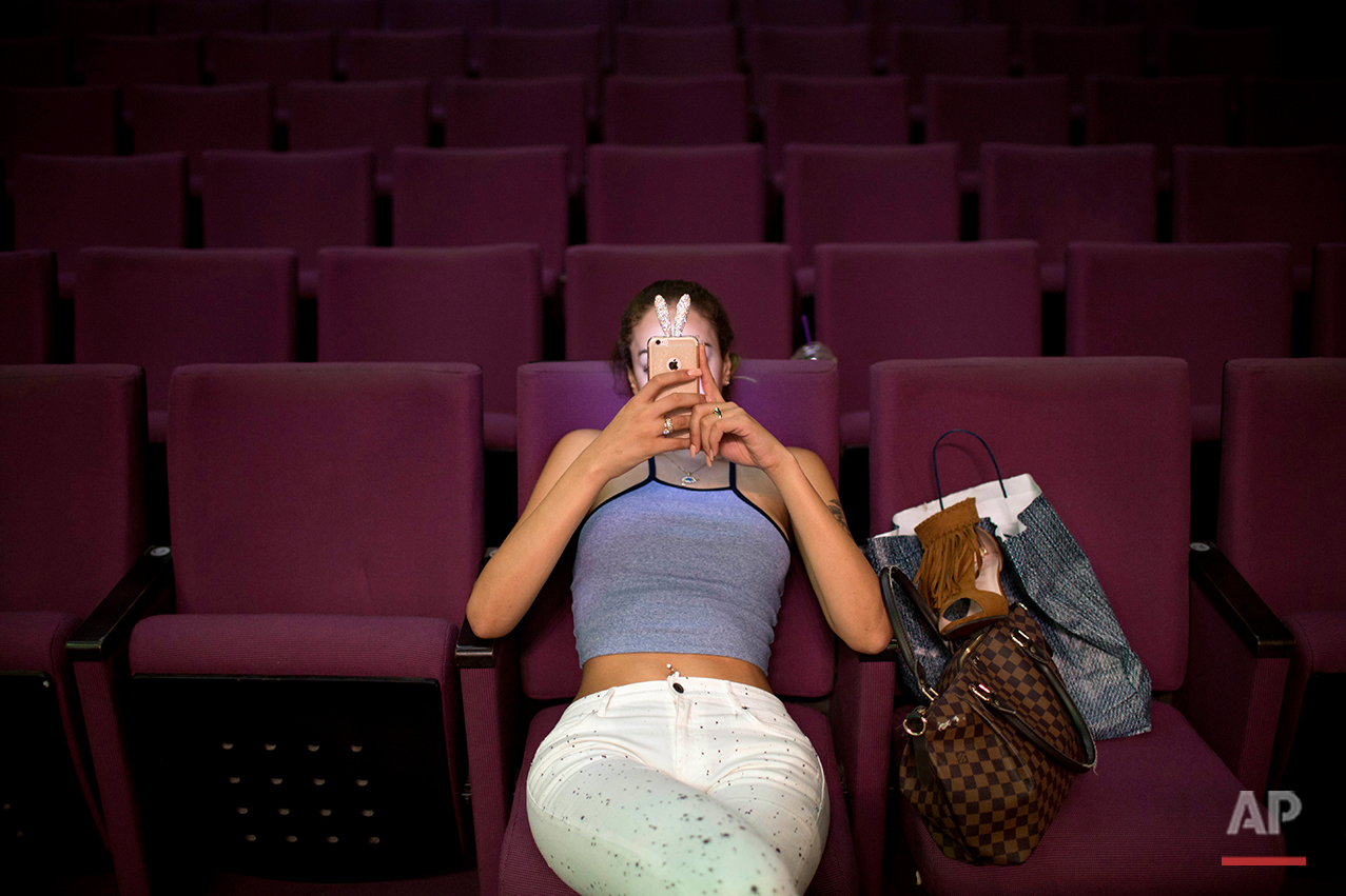 Madlen Matar, a contestant in the first Miss Trans Israel beauty pageant, uses her smartphone during rehearsal in Tel Aviv, Israel on Thursday, May 26, 2016. The pageant will be held at HaBima, Israel's national theater, in Tel Aviv on Friday. Tel Aviv has emerged as one of the world's most gay-friendly travel destinations, standing in sharp contrast to most of the rest of the Middle East, where gays can face persecution. (AP Photo/Oded Balilty)