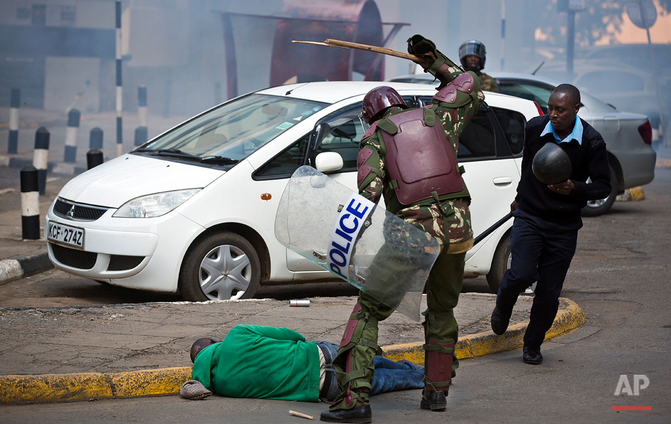 In this photo taken Monday, May 16, 2016, a Kenyan riot policeman beats a protester with a stick, breaking the stick, before kicking him as he lies in the street after falling down while trying to flee from them, during a protest in downtown Nairobi, Kenya. In an incident that has stirred anger and condemnation across Kenya, a policeman is seen beating and kicking one protester who had fallen on a road curb, while the U.S. and human rights activists have condemned violence by Kenyan police at the opposition protest for election reforms. (AP Photo/Ben Curtis)