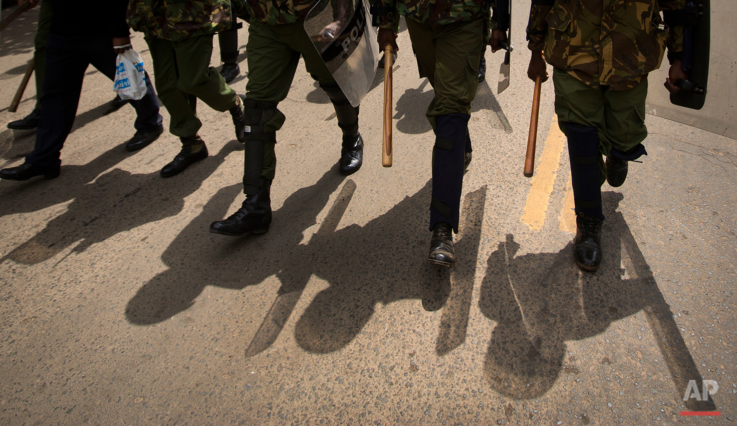 Kenyan riot police patrol and search for protesters on a street in downtown Nairobi, Kenya Monday, May 23, 2016. Kenya's police shot, beat and tear gassed opposition demonstrators across the country who tried to gather to call for the electoral commission to be dissolved due to allegations of bias and corruption. (AP Photo/Ben Curtis)