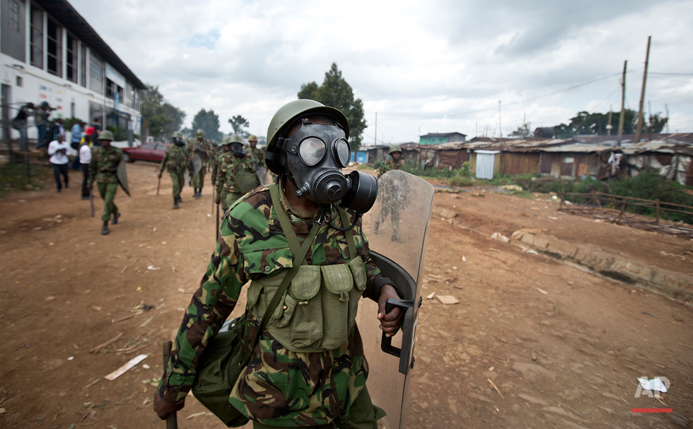 A Kenyan policeman wearing a gas mask chases protesters throwing rocks, in the Kibera slum of Nairobi, Kenya, Monday, May 23, 2016. Kenya's police shot, beat and tear gassed opposition demonstrators across the country who tried to gather to call for the electoral commission to be dissolved due to allegations of bias and corruption. (AP Photo/Ben Curtis)