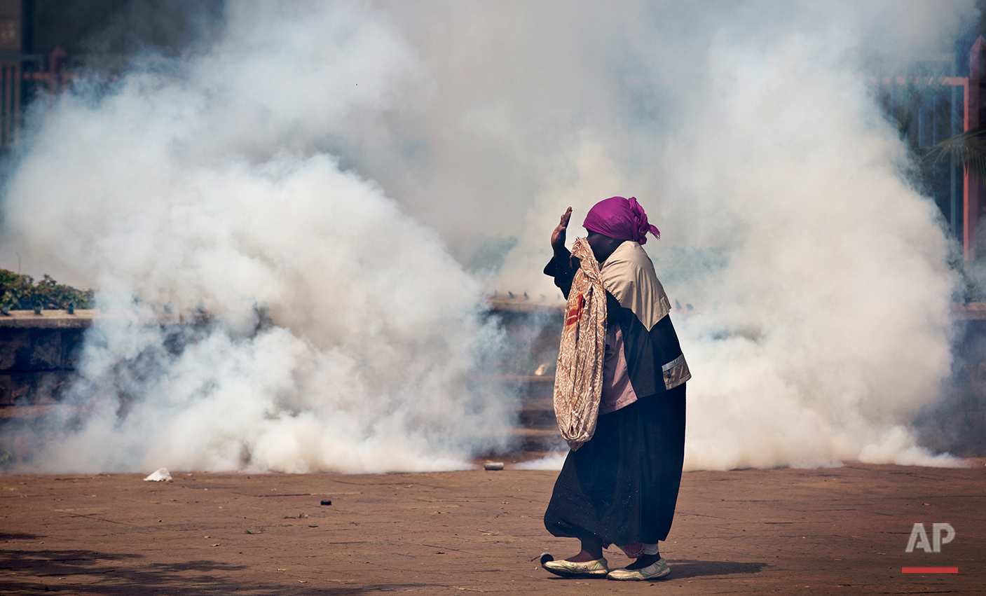 An elderly woman caught up in the clashes holds her hands in the air as a riot policeman approach amidst clouds of tear gas, during a protest in downtown Nairobi, Kenya Monday, May 16, 2016. Kenyan police have tear-gassed and beaten opposition supporters during a protest demanding the disbandment of the electoral authority over alleged bias and corruption. (AP Photo/Ben Curtis)