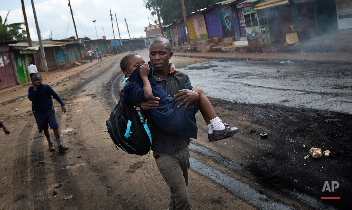 A man carries a schoolgirl overcome by tear gas to safety, past the charred remains of a burning barricade, as police firing tear gas engage protesters throwing rocks in the Kibera slum of Nairobi, Kenya Monday, May 23, 2016. Kenya's police shot, beat and tear gassed opposition demonstrators across the country who tried to gather to call for the electoral commission to be dissolved due to allegations of bias and corruption. (AP Photo/Ben Curtis)