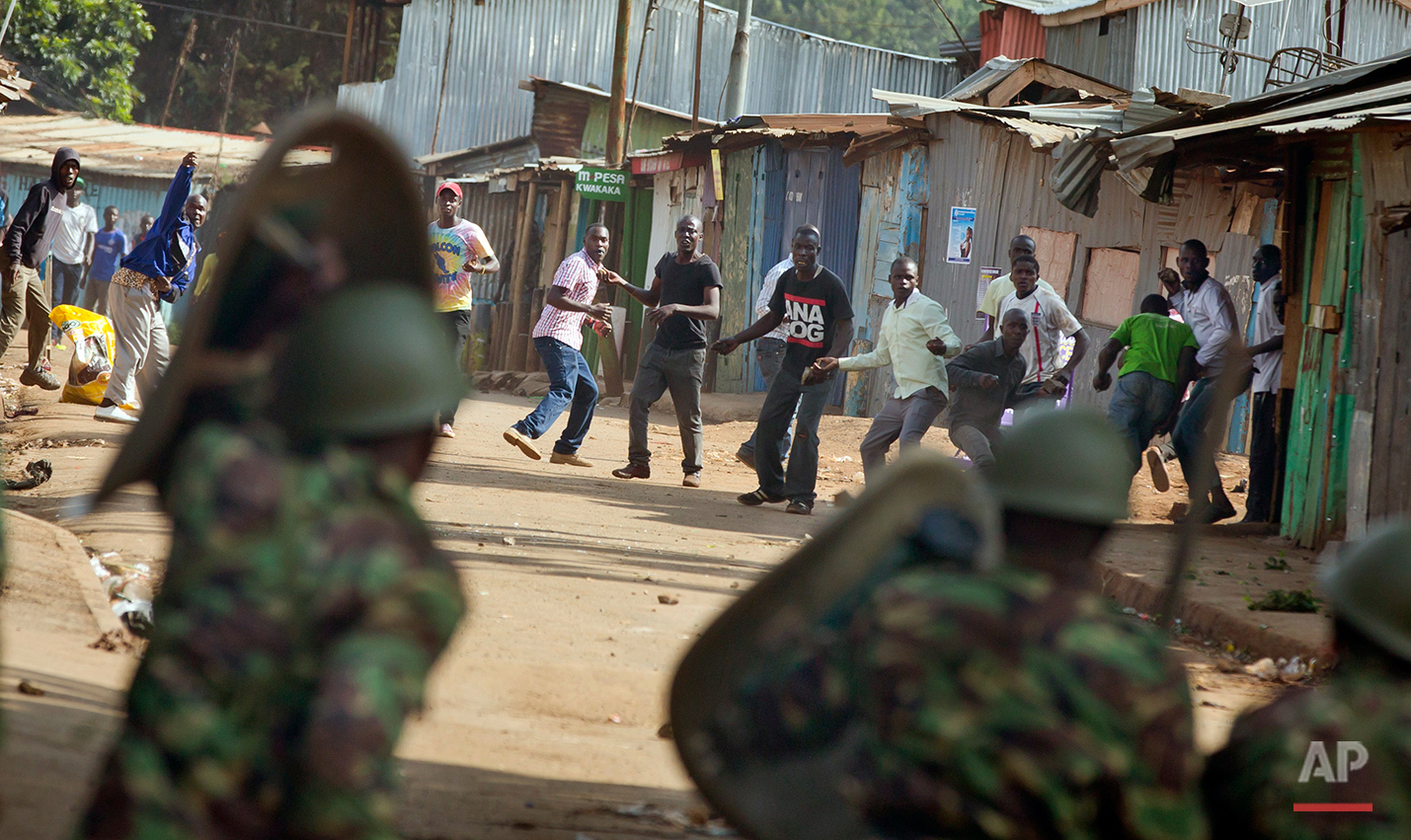 Opposition protesters throw rocks as they engage in running battles with police firing tear gas, in the Kibera slum of Nairobi, Kenya Monday, May 23, 2016. Kenya's police shot, beat and tear gassed opposition demonstrators across the country who tried to gather to call for the electoral commission to be dissolved due to allegations of bias and corruption. (AP Photo/Ben Curtis)